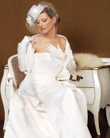 Anja Seeberg in einem bodenlangen Brautkleid. Der weiße Mini-Zylinder samt Blumenschmuck und Mini-Schleier macht dieses Ensemble