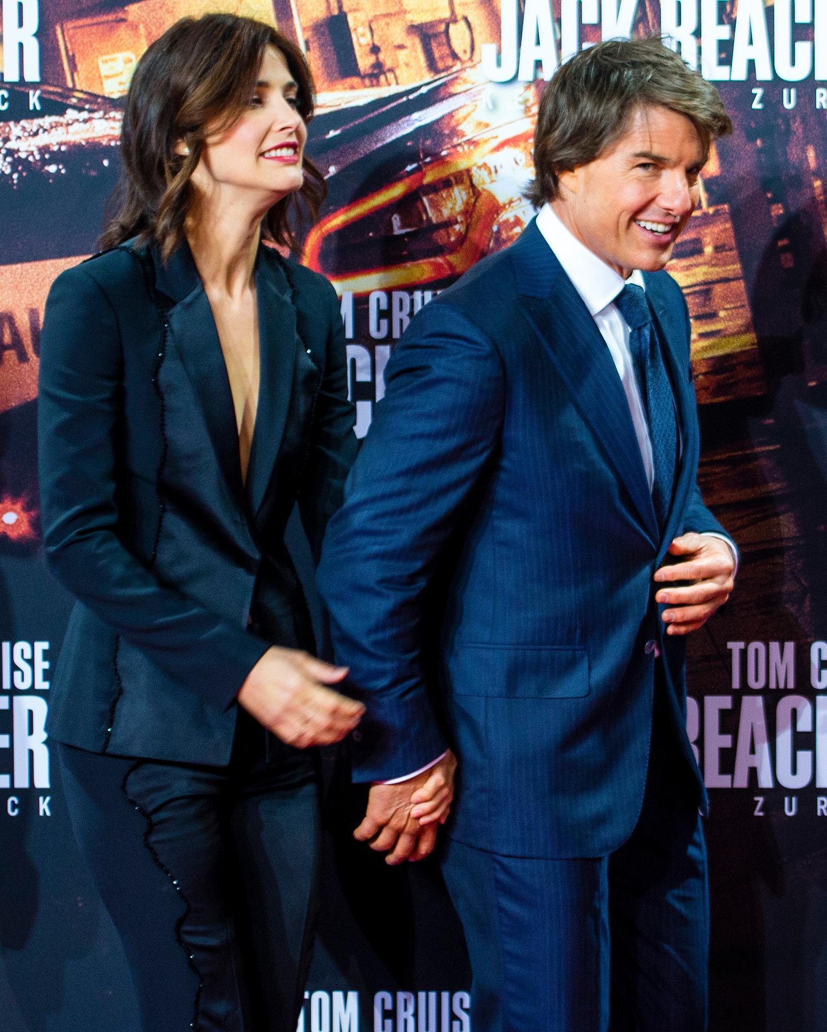 Cobie Smulders und Tom Cruise kommen Hand in Hand auf den roten Teppich.
