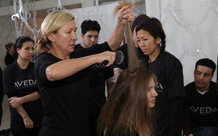 Mit einer Bürste toupiert Odile Gilbert den Hinterkopf des Models stark an.