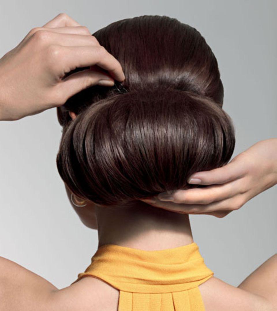 Step 4: Den Knoten vorsichtig auf die gewünschte Größe ziehen und erneut mit ausreichend Haarnadeln und etwas Haarspray fixieren