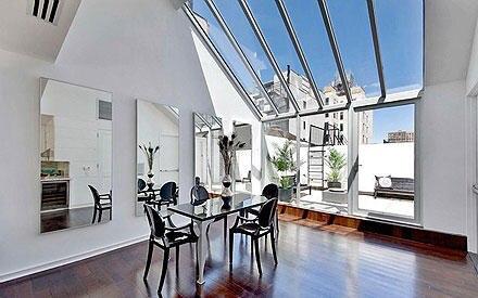 Die riesige Glasfront lässt viel Licht in den Wohbereich mit angeschlossenem Esszimmer.