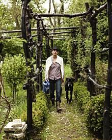 Sie pflanzt, baut, kümmert sich um die Tiere: Nadeshda Brennicke, hier mit Dogge Ganscha im selbst gezimmerten Laubengang, der d