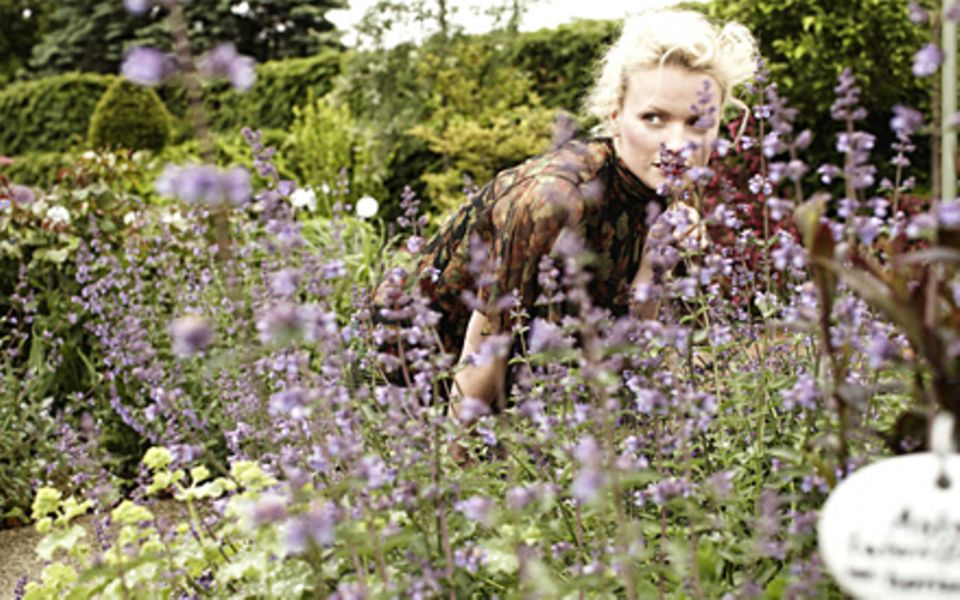 Eins und eins mit der Natur: Model Franziska Knuppe in einem Beet, das in zarten Fliedertönen gehalten ist.
