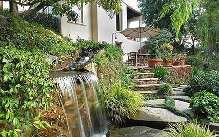 Im Garten schaffen viel Grün und ein kleiner Wasserfall eine lauschige Atmosphäre zum Entspannen.