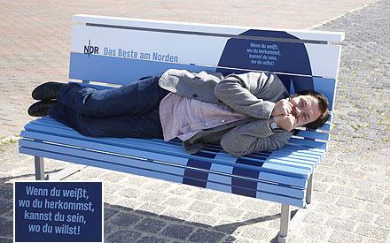 Schauspieler Charly Hübner macht auf seiner Bank im Stadthafen von Rostock Faxen.