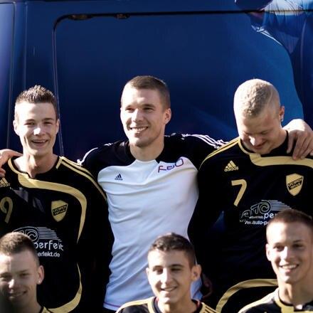 Lukas Podolski unverkleidet beim Überraschungsbesuch einer Jugend-Fußballmannschaft im Rahmen eines Werbedrehs.