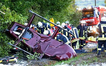 Rettungssanitäter und Feuerwehr leisten am Wrack des verunglückten Hubschraubers erste Hilfe.