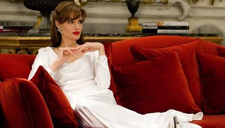 """Wie gemalt: Angelina Jolie in """"The Tourist"""" als Femme fatale auf einem roten Samtsofa und mit knallroten Lippen."""