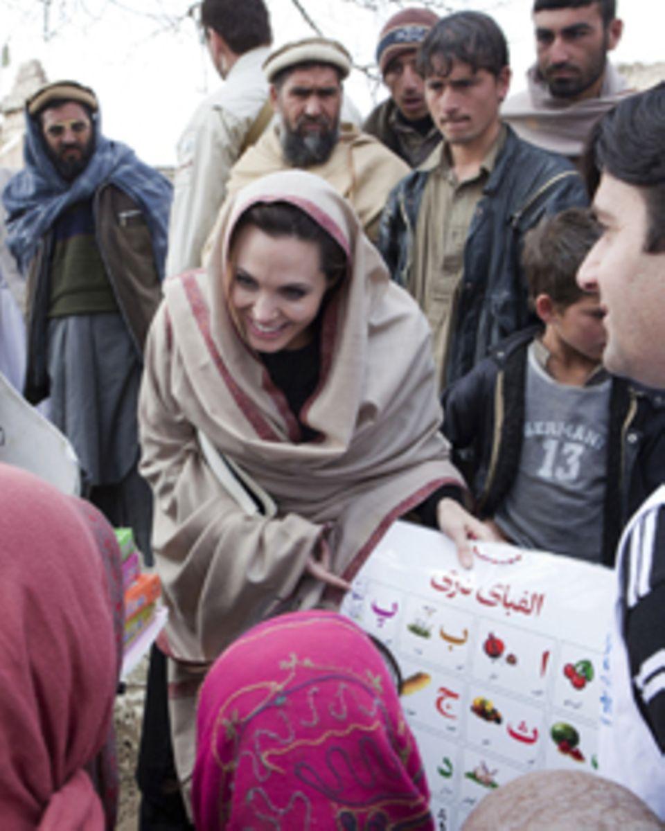 Angelina Jolie in ihrem Element: Sichtlich erfreut zeigt sie libyschen Flüchtlingskindern neues Schulmaterial.