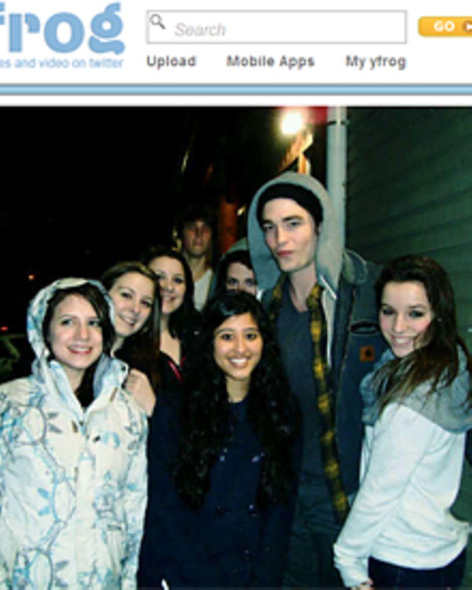 Robert Pattinson lässt sich mit einer Schar weiblicher Fans fotografieren.