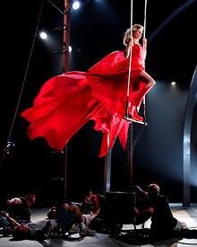 Luftige Höhen: Heidi in einem roten Kleid auf dem Trapez.