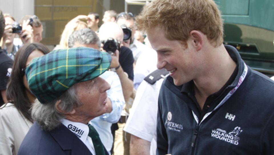 """Männer unter sich: Prinz Harry bekommt eine Führung durch das Fahrerlager von """"Formel-1""""-Legende Jackie Stewart."""