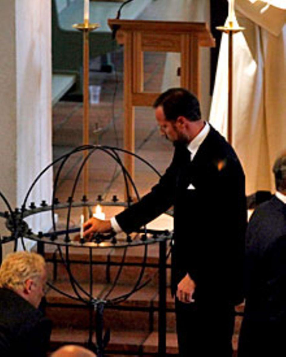 Prinz Haakon beginnt mit seiner Kerze für die Opfer.