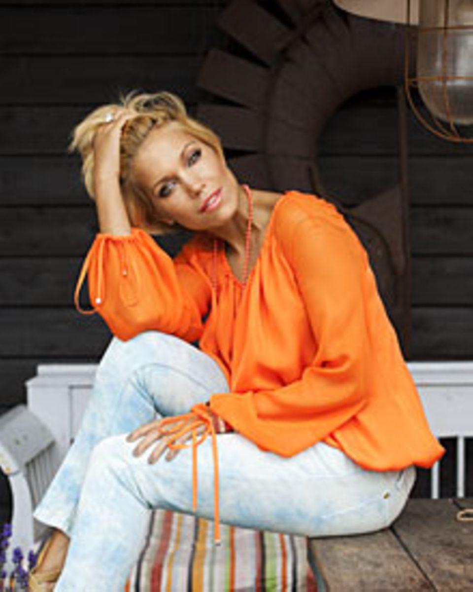 Oranje: Sylvie in der Nationalfarbe ihrer Heimat, der Niederlande (Bluse von Versace Collection, Jeans von Faith, Schuhe gesehen