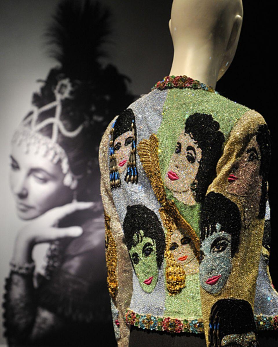 Atelier Versace entwarf die außergewöhnliche Jacke mit Konterfeis der Diva, Liz Taylor glänzte damit 1989 beim Amfar-Dinner. Die