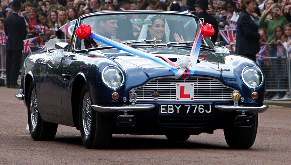 Überraschung - und die Menge jubelt: Nach dem Mittagsempfang im Buckingham                                     Palace braust das Brautpaar im Aston Martin davon.