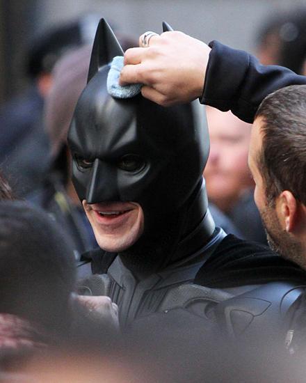 Auch Batmans Helm muss mal geputzt werden: Christian Bale lässt die Prozedur am Set in New York geduldig über sich ergehen.