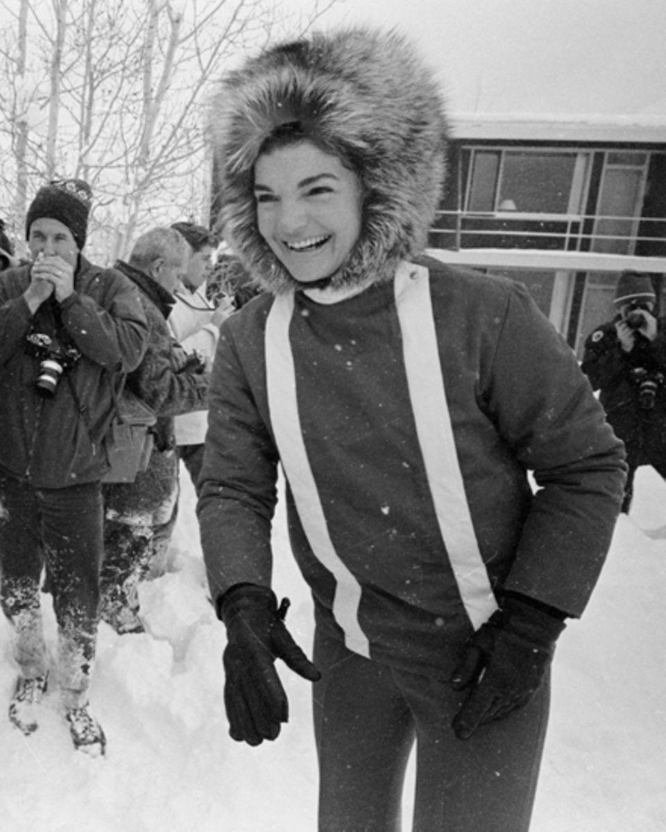 Trendsetterin Jackie Kennedy. Die pelzbemützte frühere First Lady, hier zwei Tage vor Silvester  1964, lernte in Aspen Skifahren.