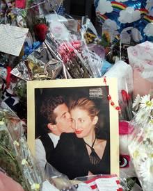 Blumen und Kerzen legten Trauernde nach John-Johns Tod vor seinem Haus ab. Das aufgestellte Foto zeigt das Traumpaar kurz vor de