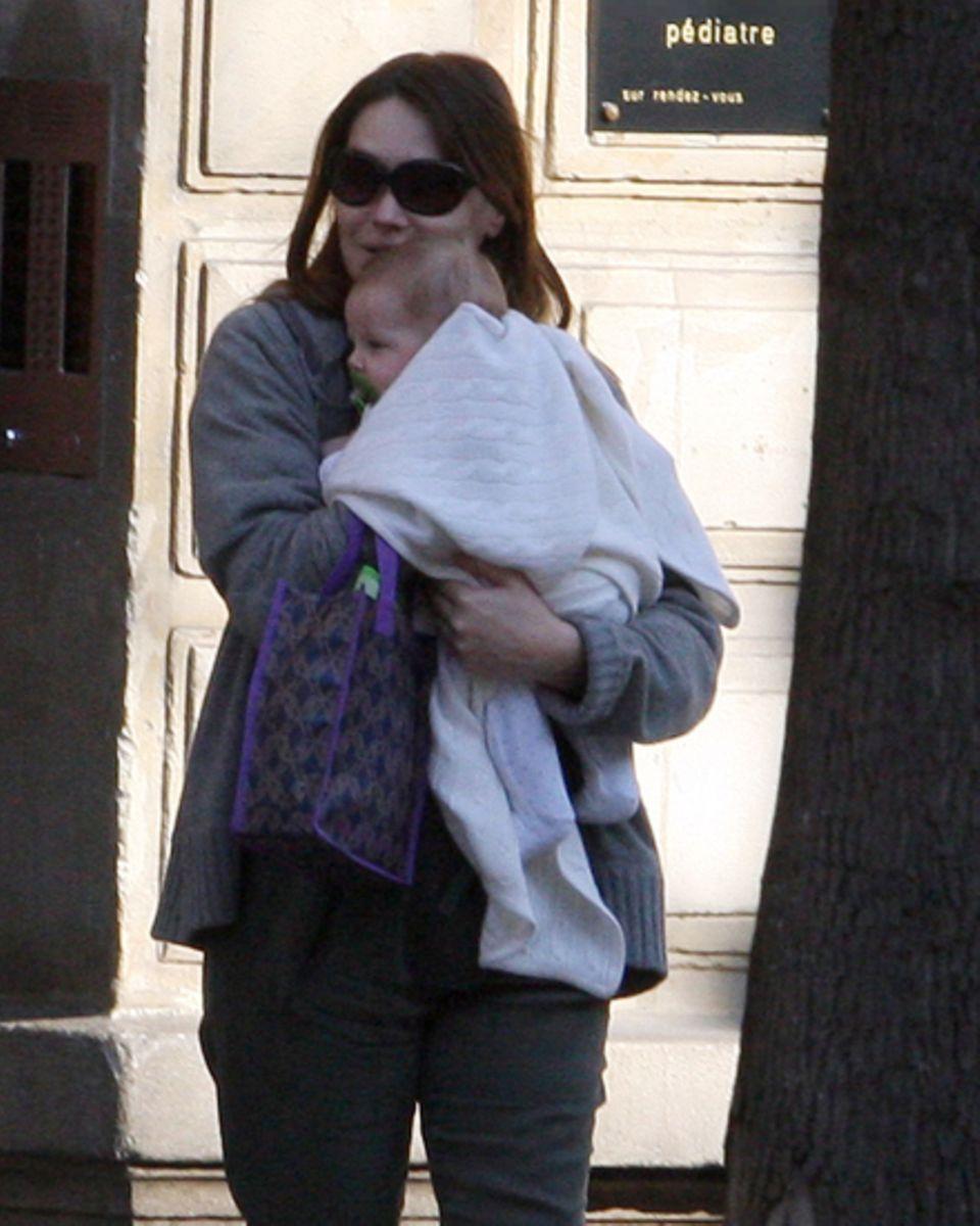 Carla Bruni trägt ihre fünf Monate alte Tochter Giulia zum Kinderarzt - ungestylt in einer lässigen Kapuzenjacke.