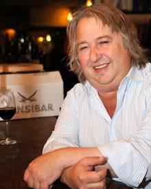 """Herbert Seckler in seiner """"Sansibar"""" bei einem Glas Rotwein."""