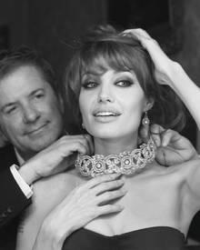 Angelina Jolie lässt sich Juwelier Robert Procop ein funkelndes Geschmeide anlegen.