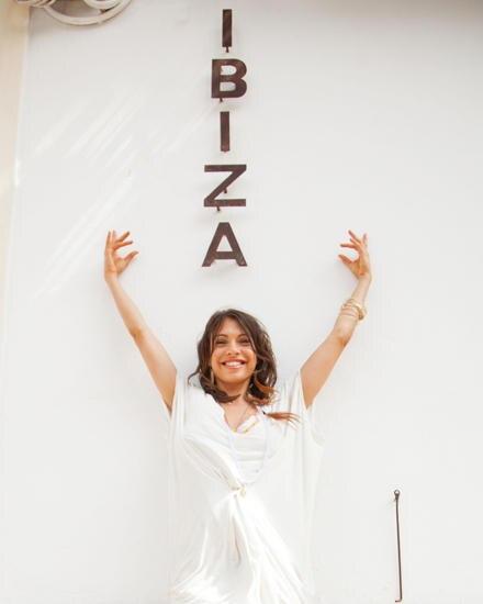"""Urlaubsfeeling: Jana in vor einem """"Ibiza"""" Schriftzug an einer Hauswand."""