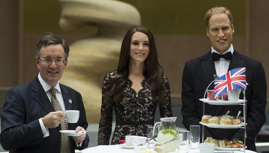 Der stellvertretende britische Botschafter Andrew Noble mit den Wachsfiguren von Kate und William in Berlin.