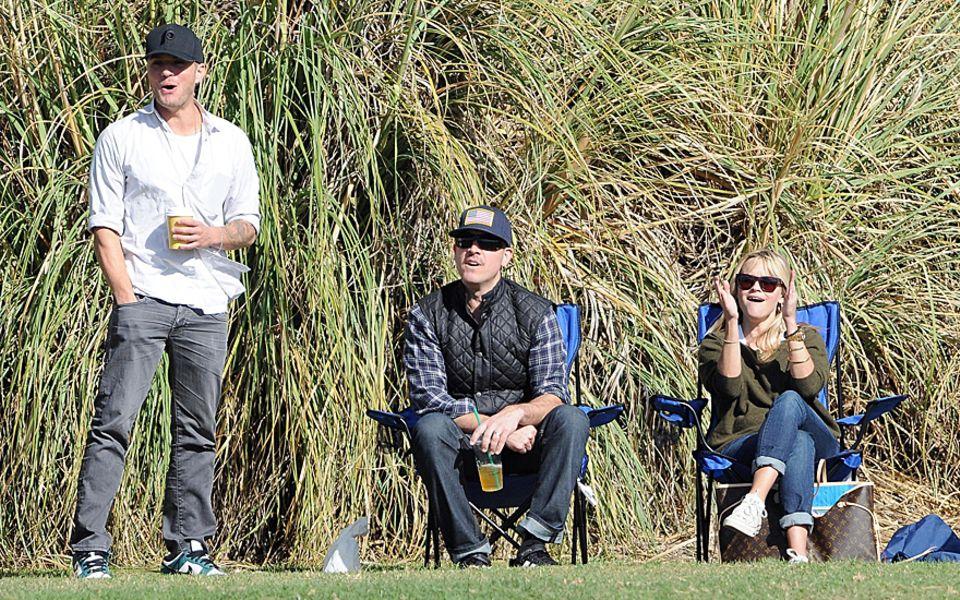 Ryan Phillippe, Jim Toth und Reese Witherspoon feuern gemeinsam den zehnjährigen Deacon beim Fußballspielen an.
