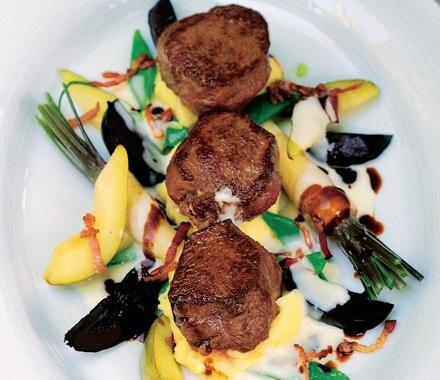 Rehmedaillons mit Birnen, Bohnen und schwarzen Nüssen.