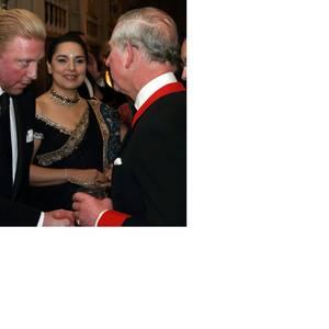 Ein Handschlag zwischen Prinz und Tennis-Star: Prinz Charles, im Dinner-Jacket mit rotem Kragen und Ärmelumschlägen, hält Small-Talk mit Boris Becker. Neben dem deutschen Tennis-Star steht seine Frau Lilly.