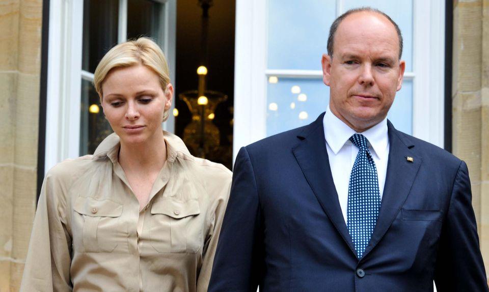 Nachdenklich blickt die Fürstin 2012 bei einem Termin in Stuttgart zu Boden, Albert wirkt distanziert. Ganz anders Mitte Dezember bei einem Charity-Termin in Monaco, wo Charlène geheimnisvoll lächelt.