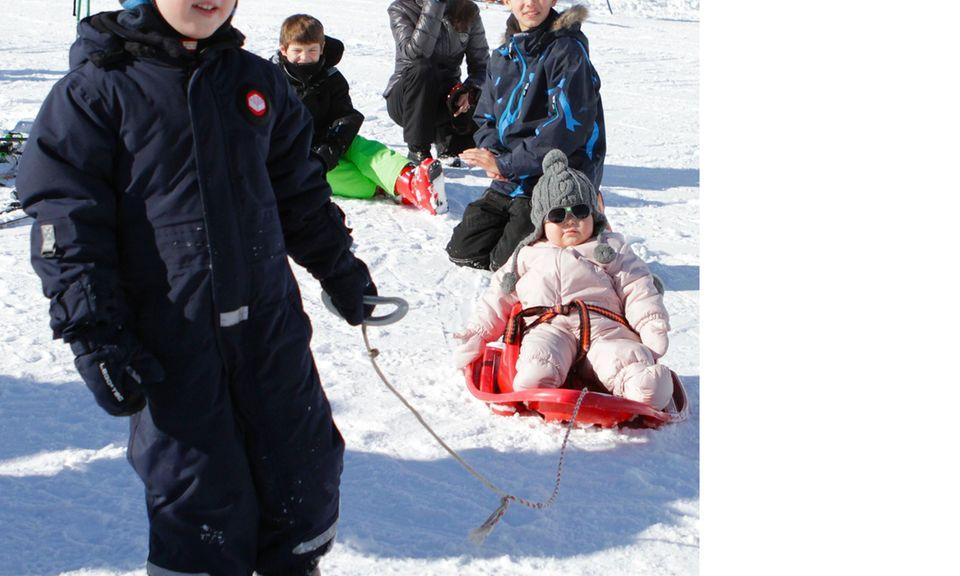 Prinz Henrik zieht seine kleine Schwester Athena auf dem Schlitten durch den Schnee.
