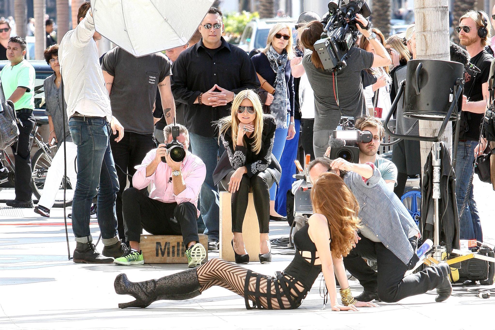 """Action beim Dreh in Beverly Hills: Kandidatin Carolin rekelt sich für die Kamera des Fotografen auf dem Asphalt, """"GNTM""""- Jurychefin Heidi Klum verfolgt die Szene mit prüfendem Blick."""