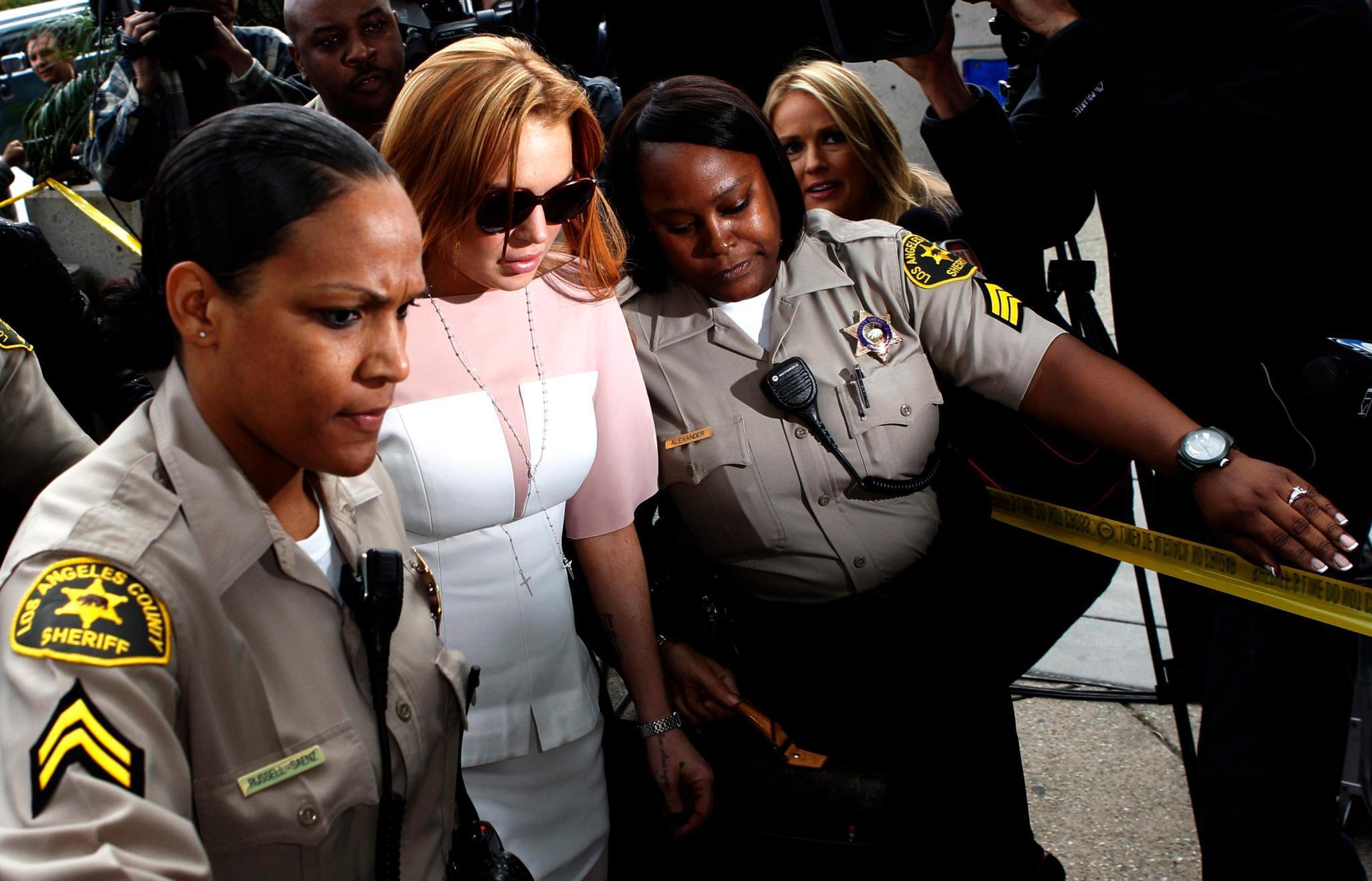 Lindsay Lohan betritt am 18. März 45 Minuten zu spät und von Polizistinnen begleitet das Gericht in Los Angeles.