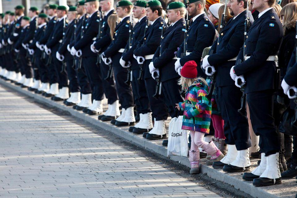 Ein kleines Mädchen hat sich zwischen der Ehrenwache anlässlich der Beerdigung der schwedischen Prinzessin LIlian hindurchgewagt und wartet auf die Prozession mit dem Sarg der Adligen.