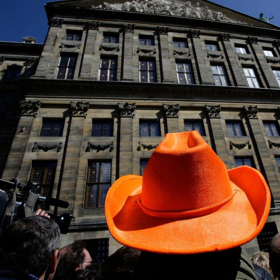 Ein Mann mit orangefarbenem Hut wartet schon am Vorabend er Abdankung vor dem königlichen Palast in Amsterdam.