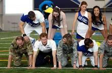 Prinz Harry wirkt als Fundament einer menschlichen Pyramide. Den weiblichen Cheerleadern scheint es zu gefallen.