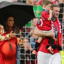 12. Mai 2013: Mit Sohn Kai auf dem Arm hat Wayne Rooney nach dem Spiel von Manchester United gegen Swandea offenbar keine Möglichkeit mehr, seiner hochschwangeren Frau Coleen den Schirm zu halten.