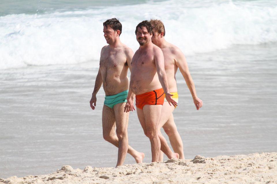 Ed Helms und Zach Galifianakis spazieren in ihren knappen, bunten Badehosen am Strand entlang.