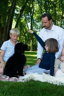 """Im Jahr 2009 entstand dieses Bild der norwegischen Kronprinzenfamilie mit ihrem neuen Hund """"Milly Kakao"""", einem Labradoodle, der von den Kindern sofort heiß geliebt wurde und seitdem immer mal wieder auf Bildern der Königsfamilie in ihrer Freizeit zu sehen ist."""