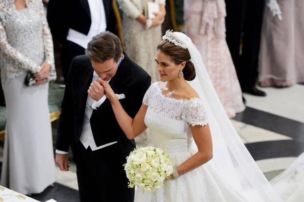 Ein ergriffener Bräutigam küsst die Hand seiner Braut, die sich insgesamt sehr königlich zeigt.