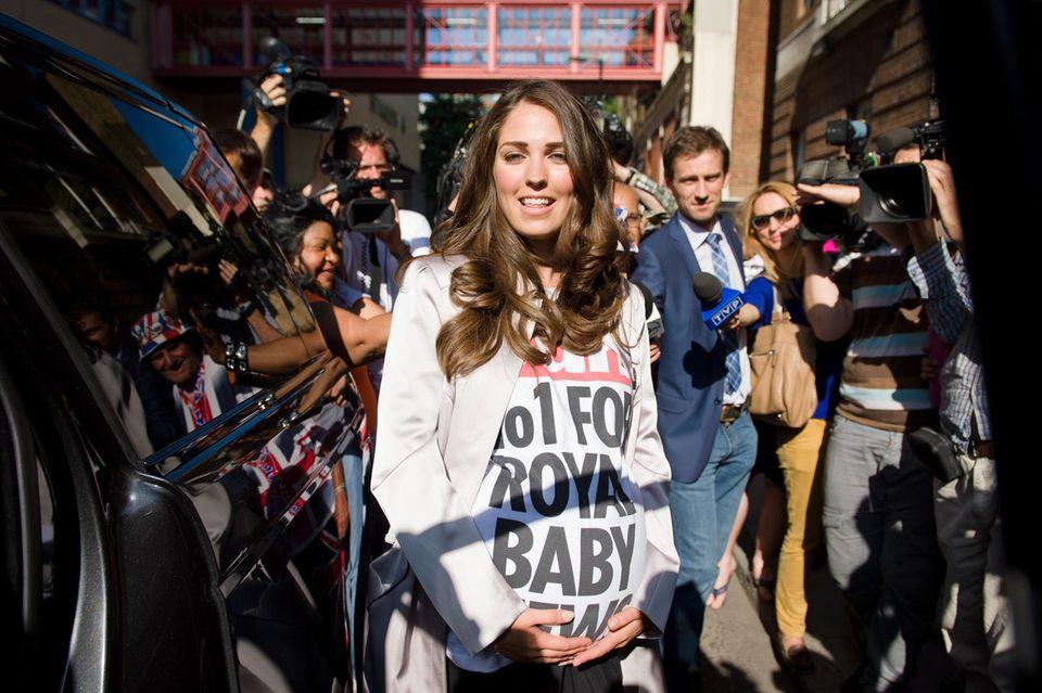 """Als die Kate-Doppelgängerin ihren mantel öffnete, präsentierte sie darunter das Werbeshirt ihrer Auftraggeber: """"The Sun"""" - No. 1 for Royal Baby News"""" war da zu lesen. Die Zuschauer nahmen es mit Humor."""