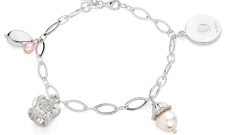 Im Stil eines Bettelarmbands verkörpert das Armband von Claudia Bradby den neuen Lebensabschnitt, den die Geburt von Baby George für William und Catherine markiert. Es trägt verschiedene royale Symbole, die Bradby seit 2007 designt hat.