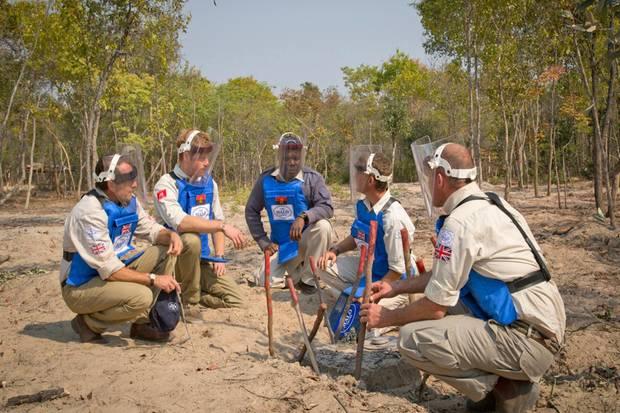 Prinz Harry verschafft sich vor Ort einen Überblick über den Fortschritt der Räumung und unterhält sich mit Experten auf einem Minenfeld in Angola.