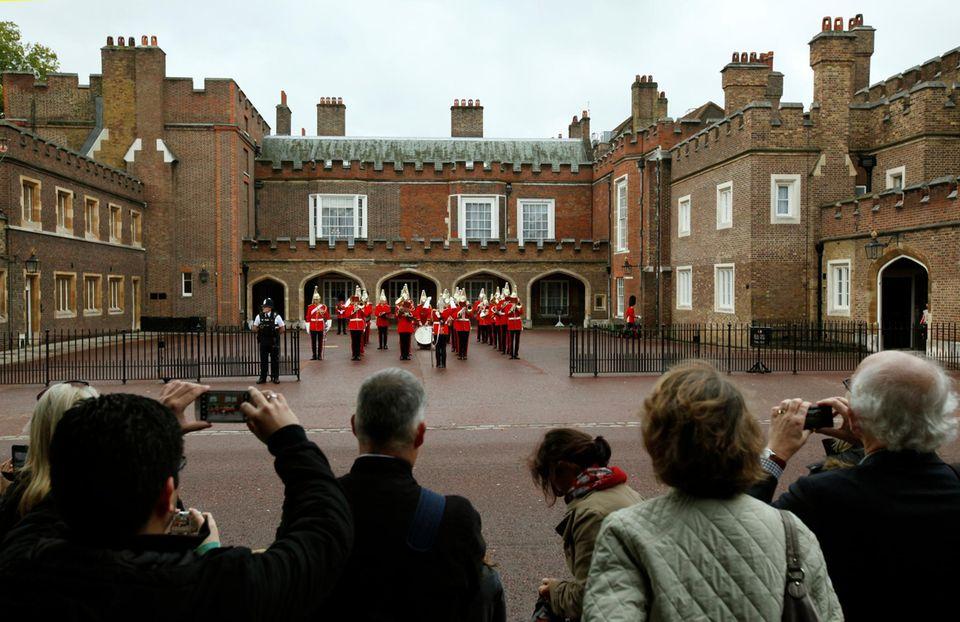 """Vor dem """"St. James Palace"""" haben sich trotz Londoner Nieselwetter viele Royalfans versammelt, um zu beobachten, wie die Taufgesellschaft vor der Taufe von prinz George von Cambridge an dem Stadtpalast ankommt."""