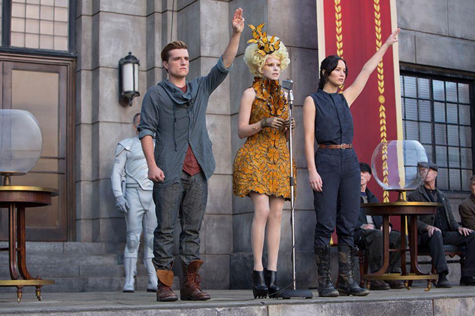 Peeta (Josh Hutcherson) und Katniss (Jennifer Lawrence) müssen erneut zu den Hungerspielen antreten. PR-Lady Effie Trinket (Elizabeth Banks) steht ihnen dabei wieder zur Seite.