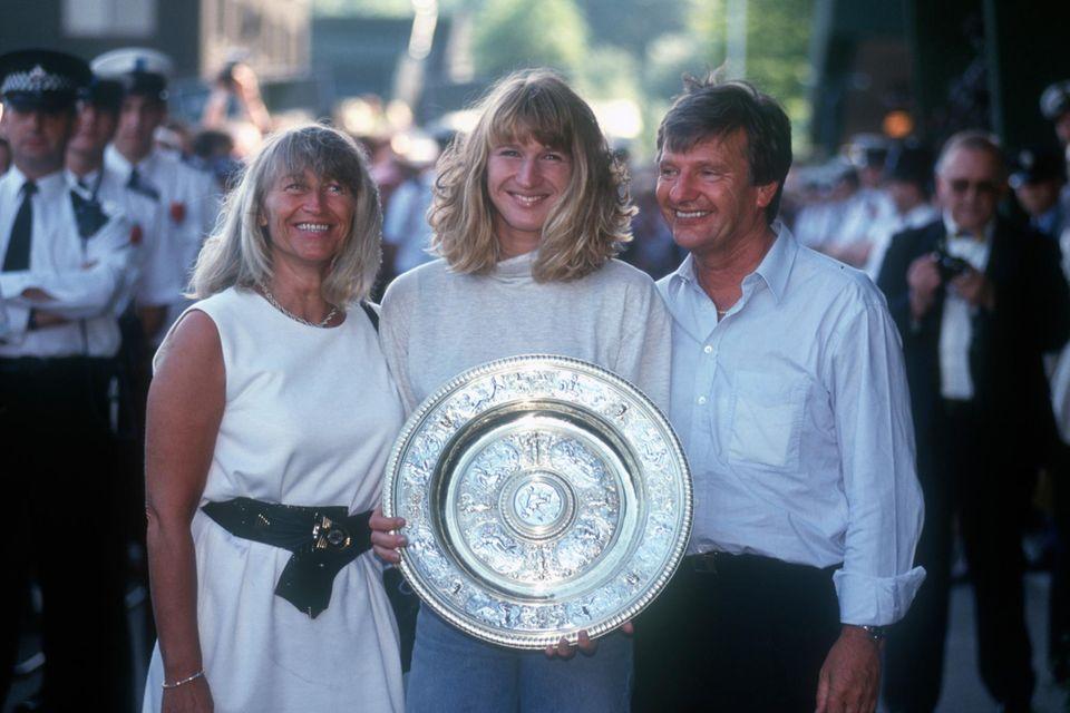 Ein Leben fürs Tennis: Mit Mutter Heidi und Vater Peter feiert Steffi Graf 1991 ihren Wimbledon-Sieg. Sie gewann allein dieses Turnier sieben Mal und war 377 Wochen die Nummer eins der Weltrangliste.