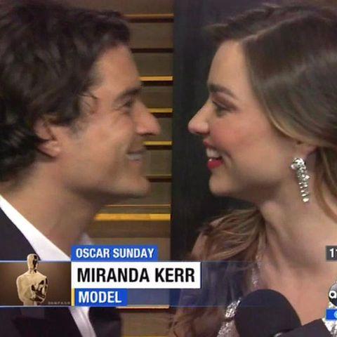 Orlando Bloom überrascht Miranda Kerr während eines Interviews.