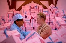 """Ein Traum in Pink: """"Agatha"""" (Saoirse Ronan) und """"Zero Moustafa"""" (Tony Revolori) tauchen in die Kuchenpackungen der Bäckerei """"Mendls"""" ein."""